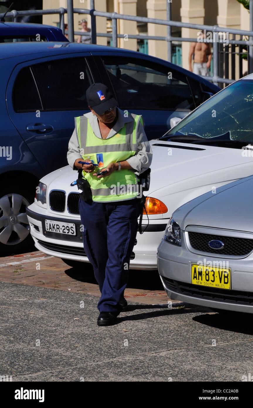 A traffic warden books a parked car at Bondi Beach near Sydney, New South Wales, Australia - Stock Image