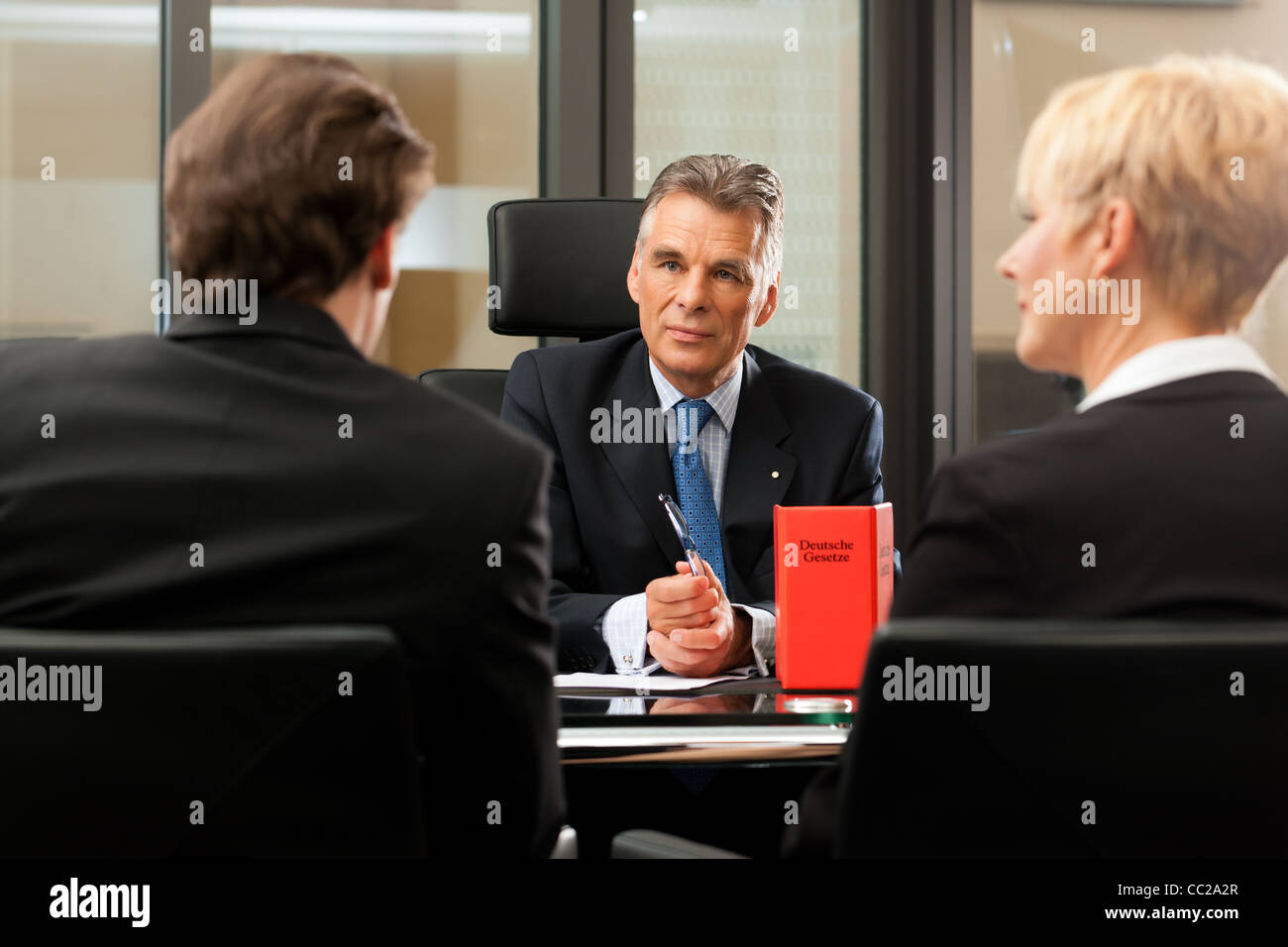 Mature lawyer or notary with clients in his office in a meeting - Stock Image