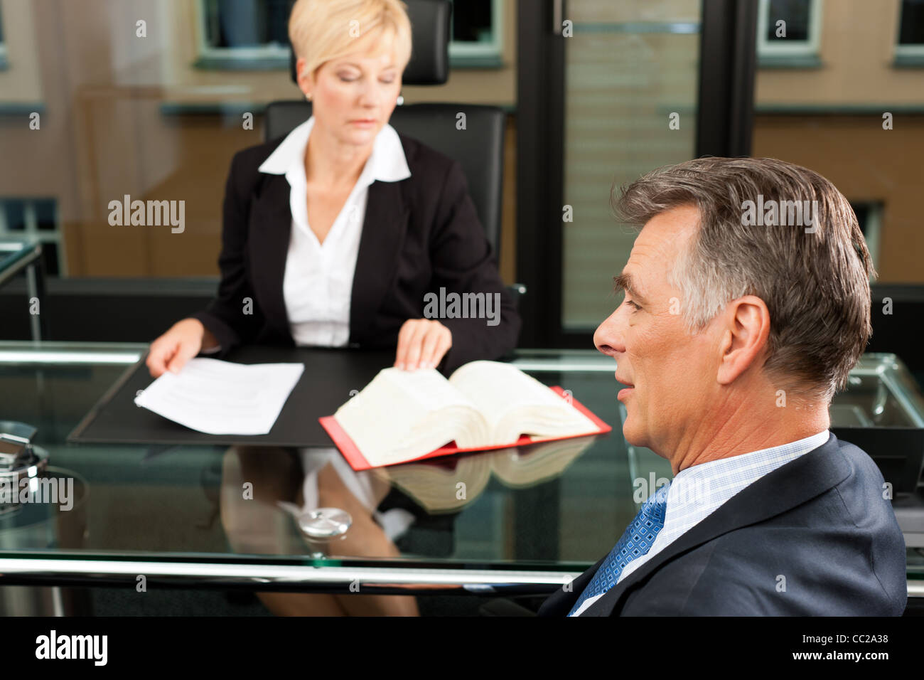 Mature female lawyer or notary with client in her office for counseling - Stock Image