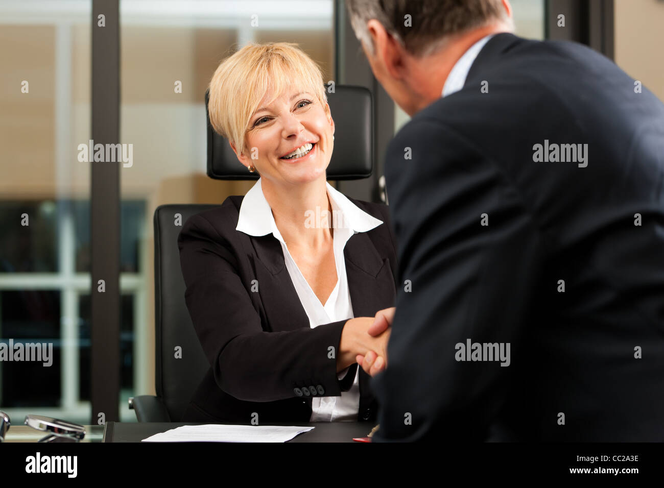 Mature female lawyer or notary with client in her office - handshake - Stock Image