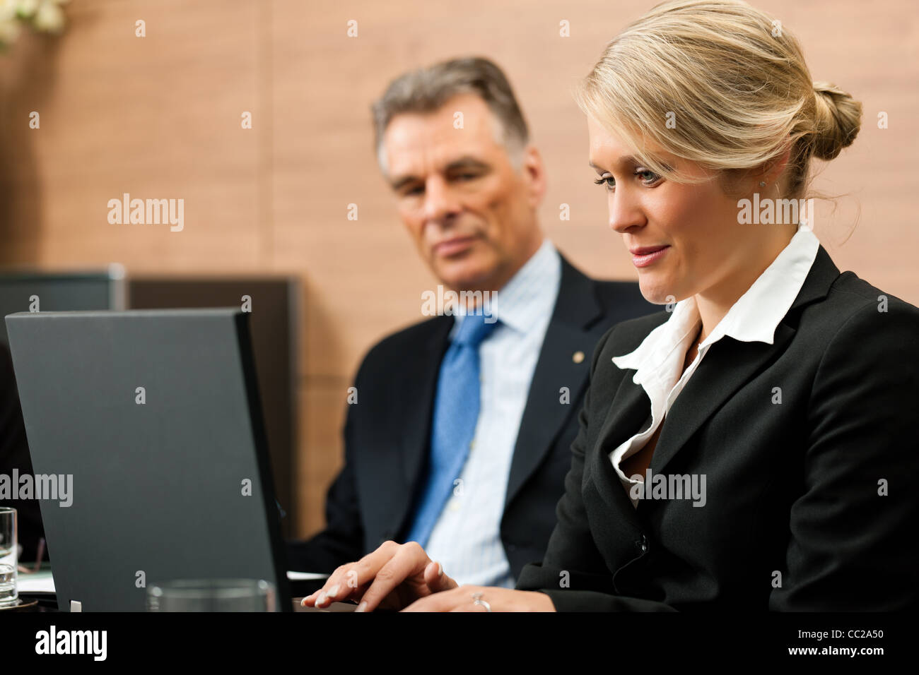 Lawyer with his secretary in his office, she is typing something - Stock Image