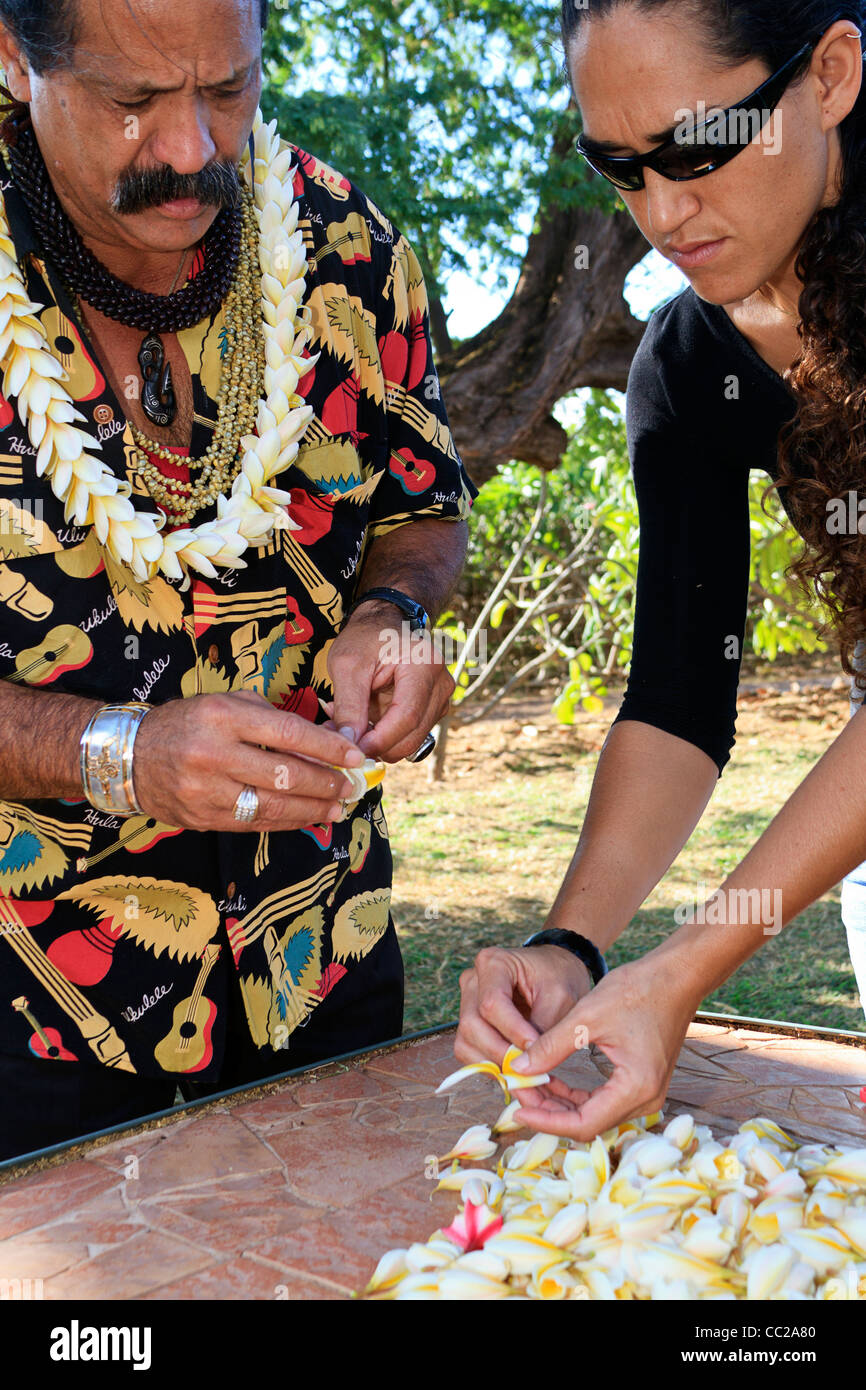 Local man and woman string plumeria (frangipani) flowers to make a lei on Molokai, Hawaii, USA. - Stock Image