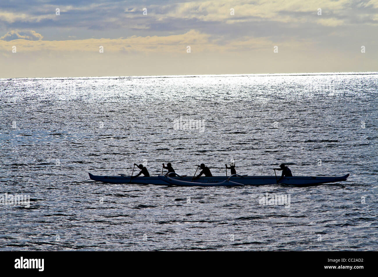 Local youths paddle a traditional outrigger Hawaiian canoe in the waters off Molokai, Hawaii, USA. - Stock Image