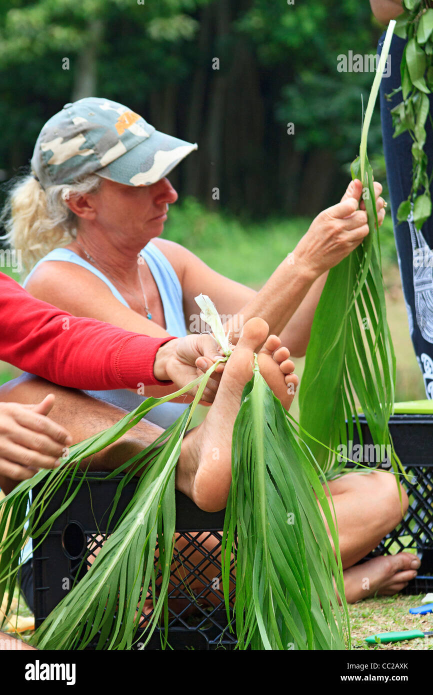 Woman visitor tries her hand at making a traditional lei, not from flowers but from ti leaves. Halawa Valley, Molokai, - Stock Image