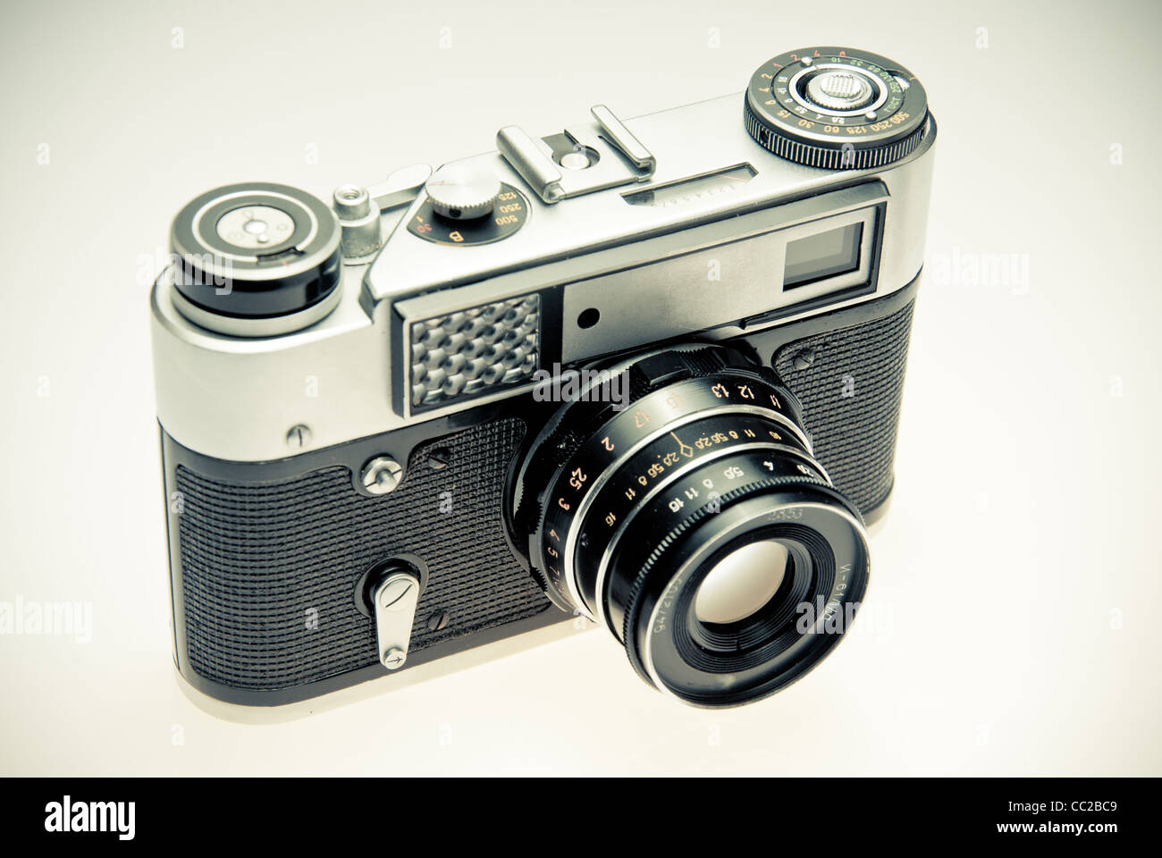 Old photography camera in vintage style over light background - Stock Image