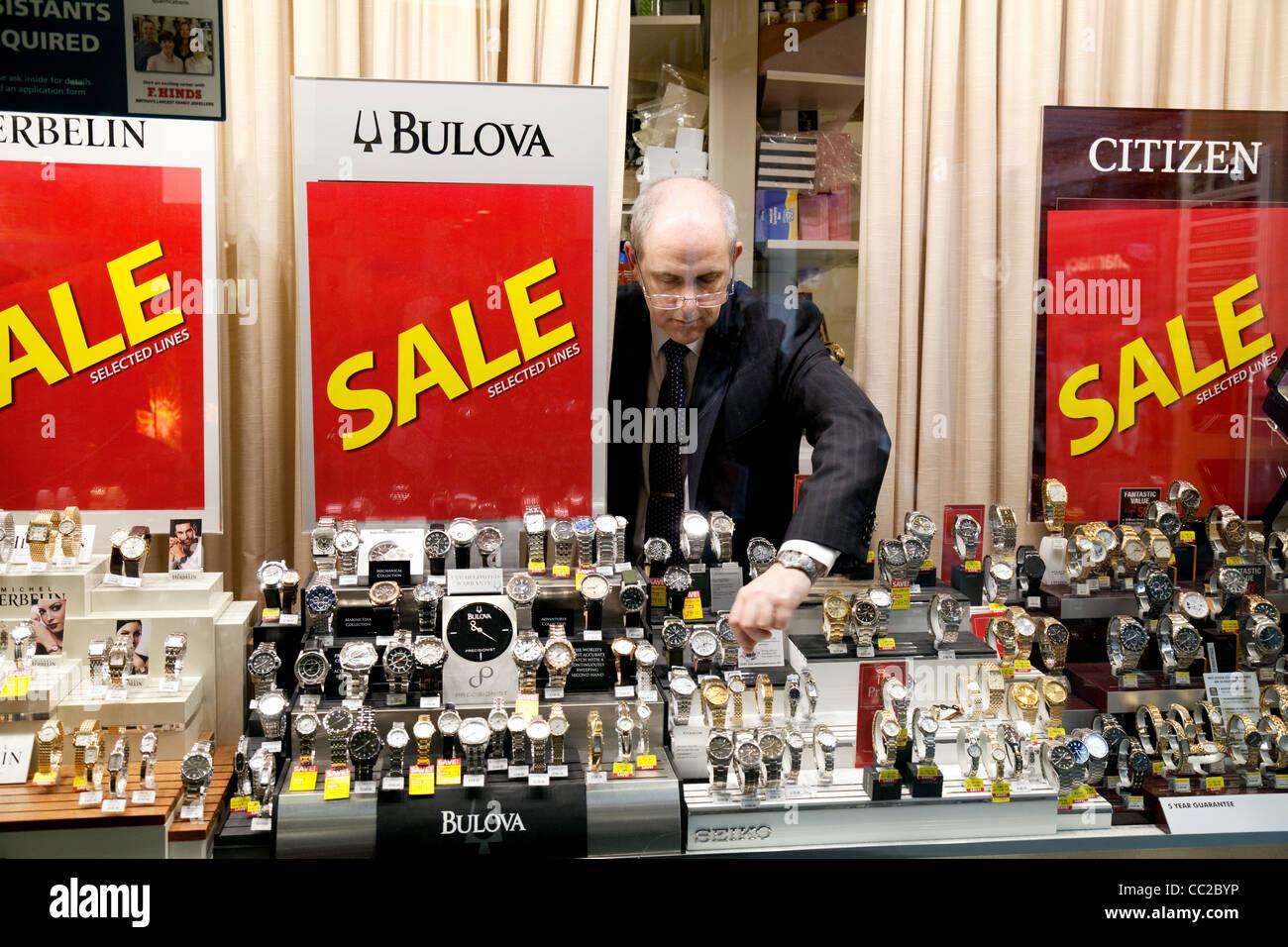 A jeweller adjusting his shop window in a sale, Cambridge UK - Stock Image