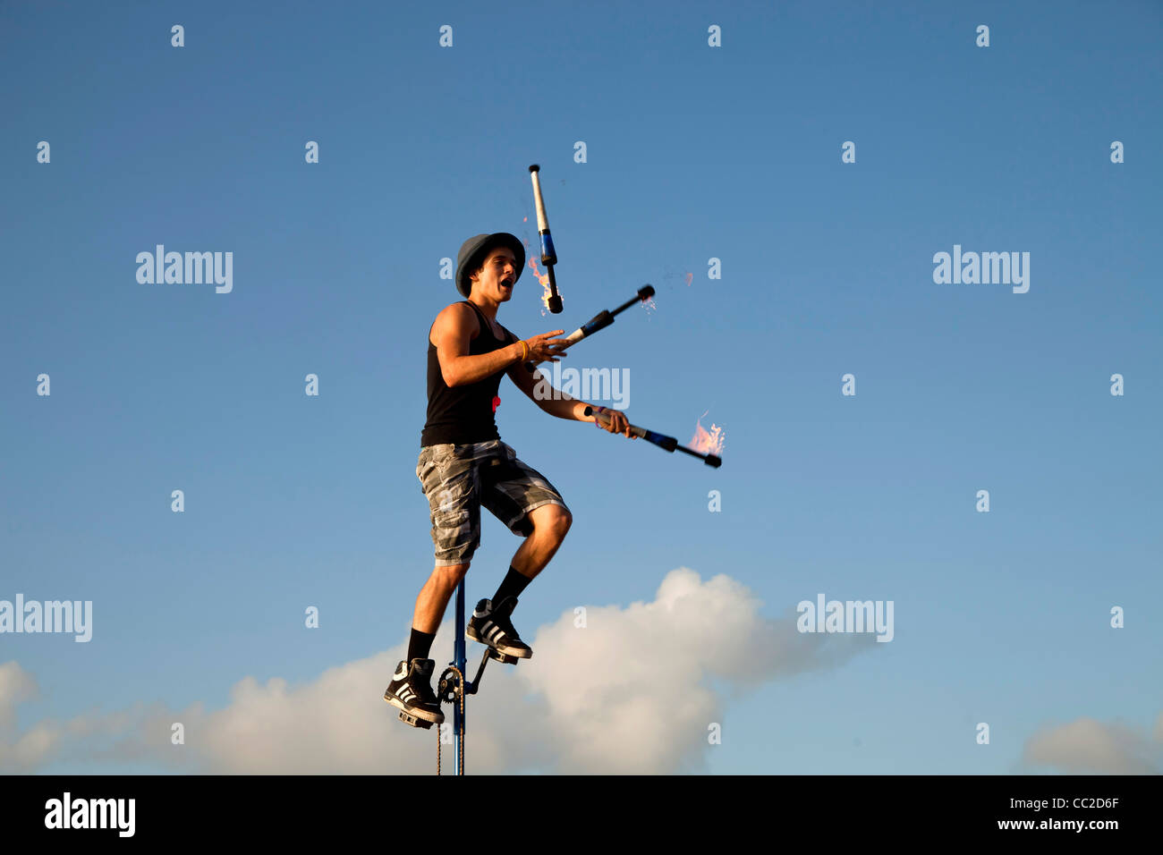 Street performer on Unicycle juggling with torch at Mallory Square in Key West, Florida Keys, Florida, USA - Stock Image
