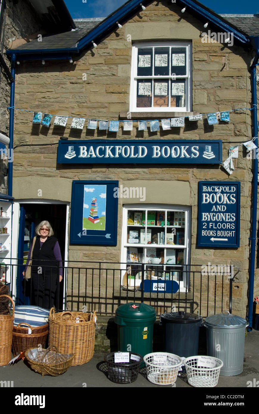 Woman standing in the doorway of a bookstore in Hay-on-Wye, the Welsh border town which has become a booklovers' - Stock Image