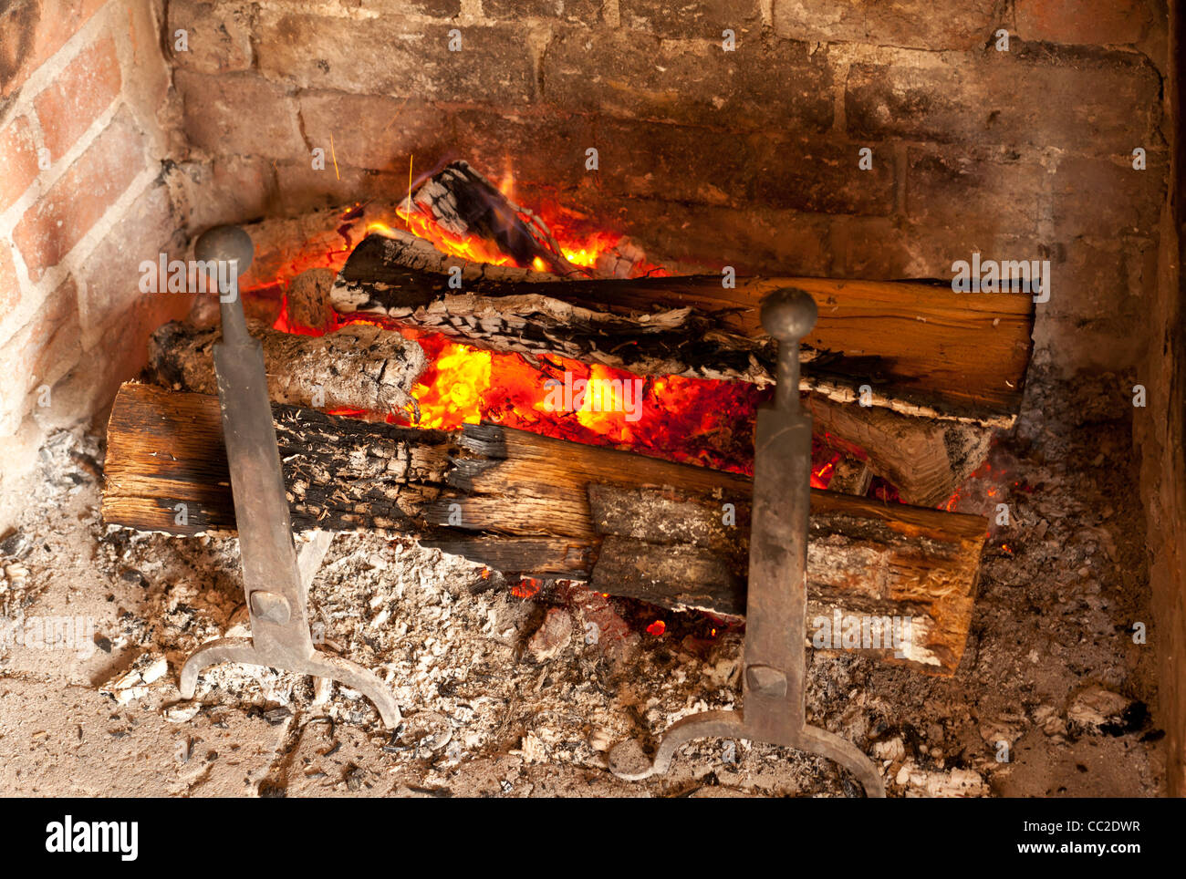 Brick fireplace with wooden logs burning - Stock Image