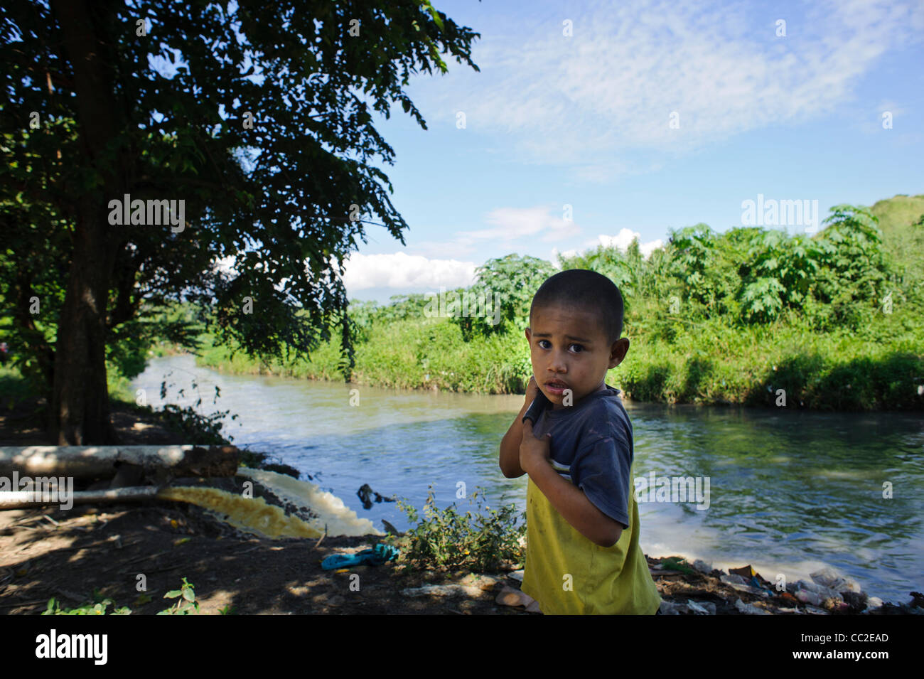 Water pollution with young boy beside effluent pipe draining into river in San Pedro Sula - Stock Image