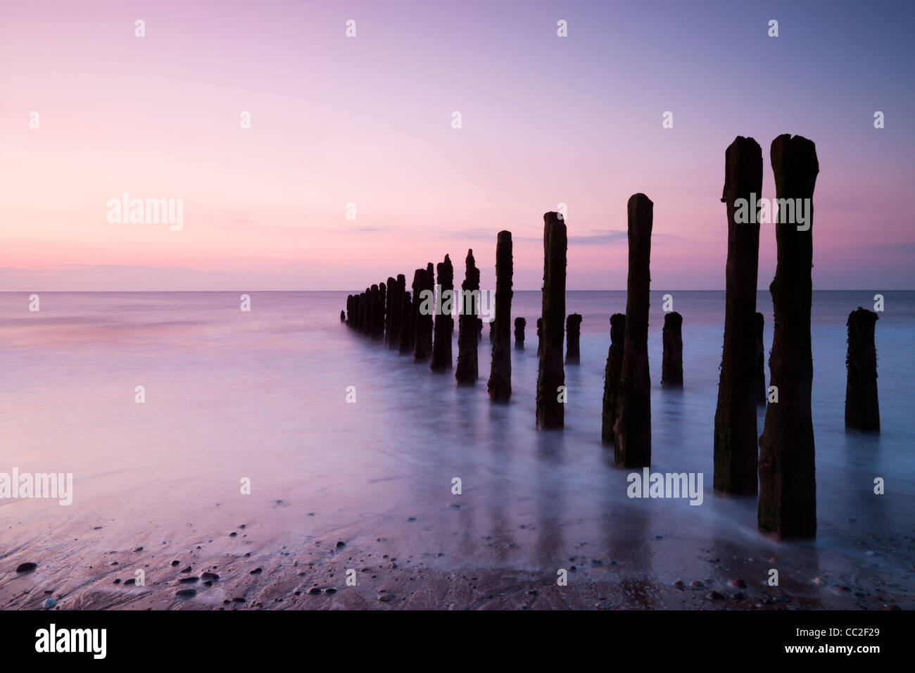 Old sea defences at dawn, smooth water from long exposure. - Stock Image