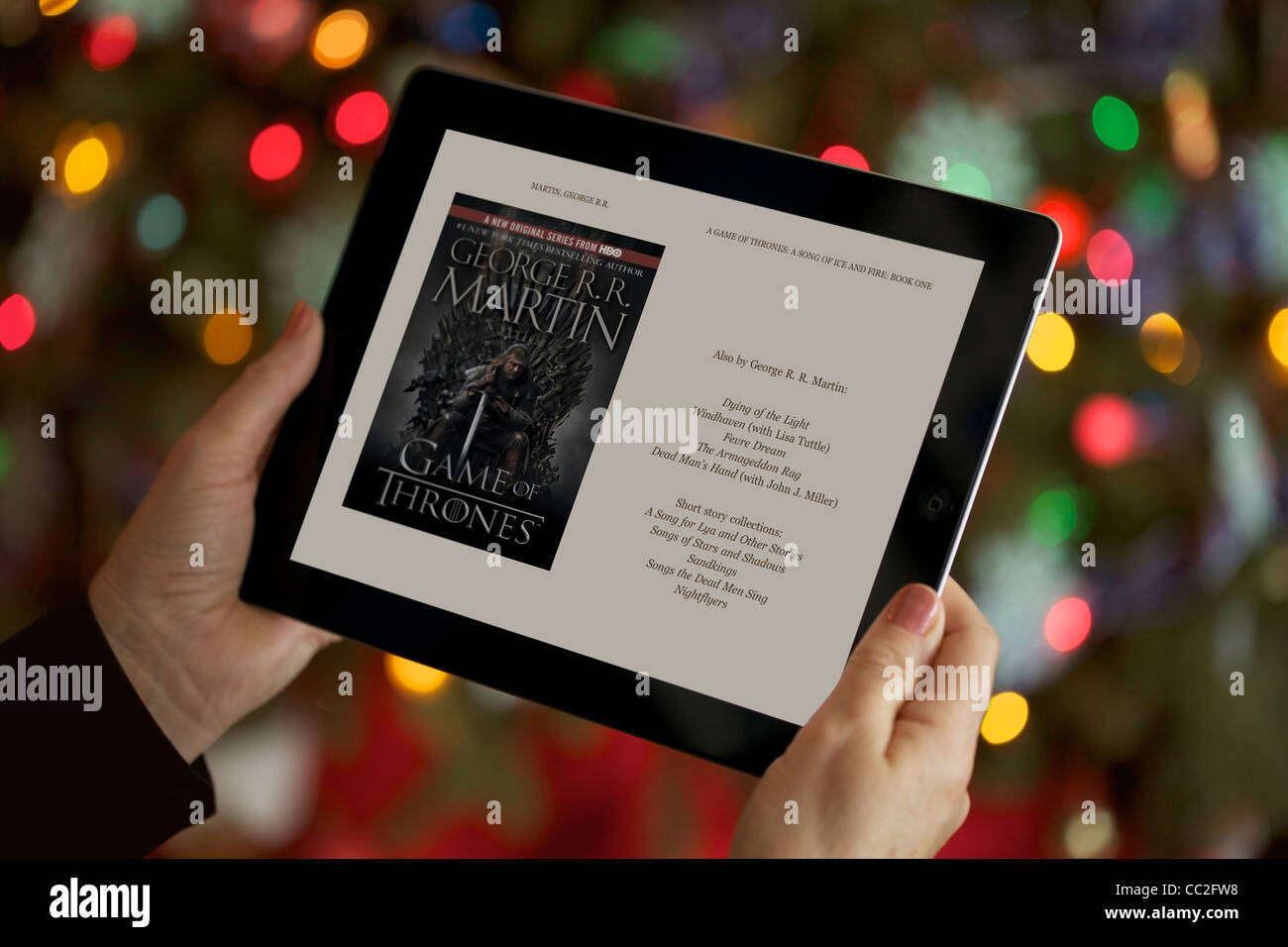 Close up view of a woman relaxing in the living room while reading 'Games of Thrones' on her iPad 2 - Stock Image