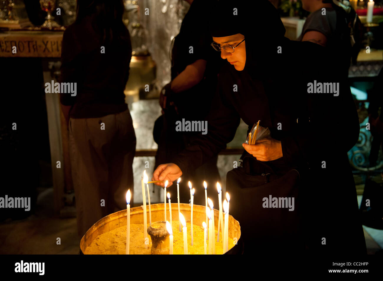 A nun lights candles in the Church of the Holy Sepulchre, traditional site of the death, burial, and resurrection - Stock Image