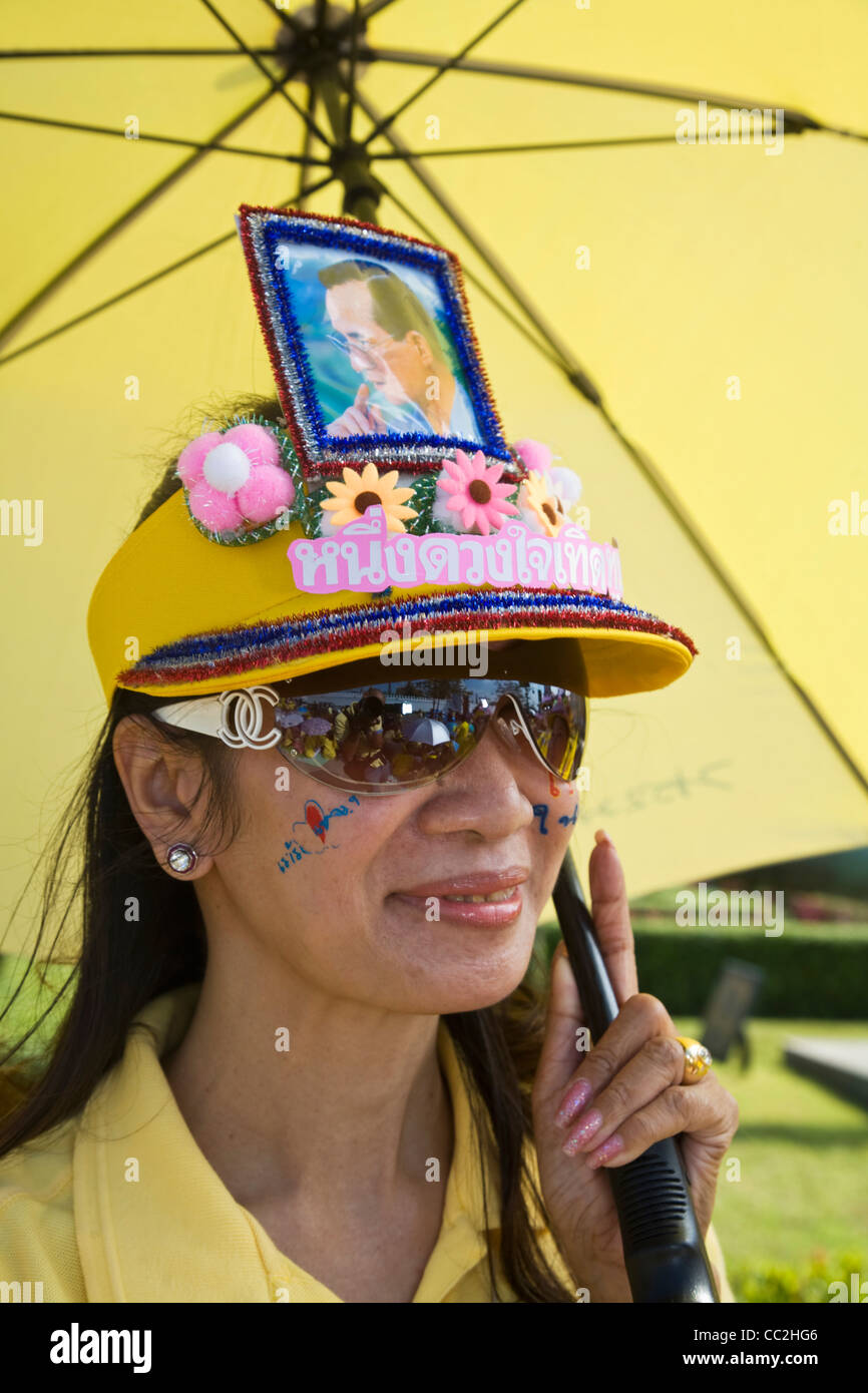 Woman wearing cap decorated with an image of the monarch, King Bhumibol Adulyadej.  Bangkok, Thailand - Stock Image
