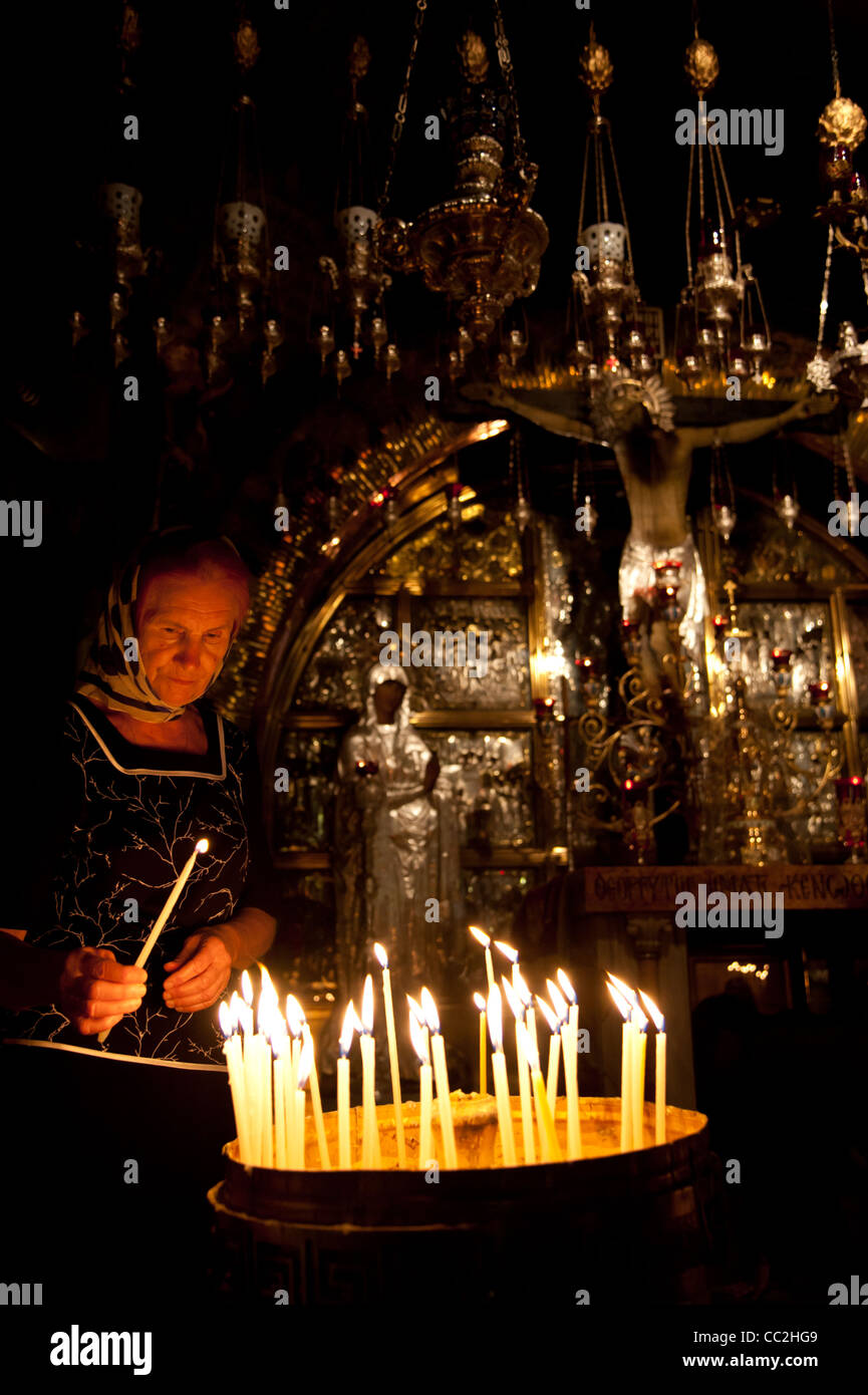 Pilgrims light candles in the Church of the Holy Sepulchre, traditional site of the death, burial, and resurrection - Stock Image