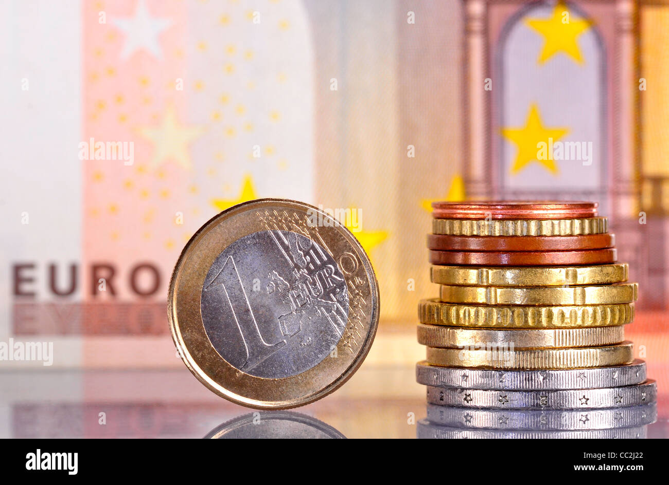 One Euro coin, next to a pile of coins with a 50 euro bill behind - Stock Image