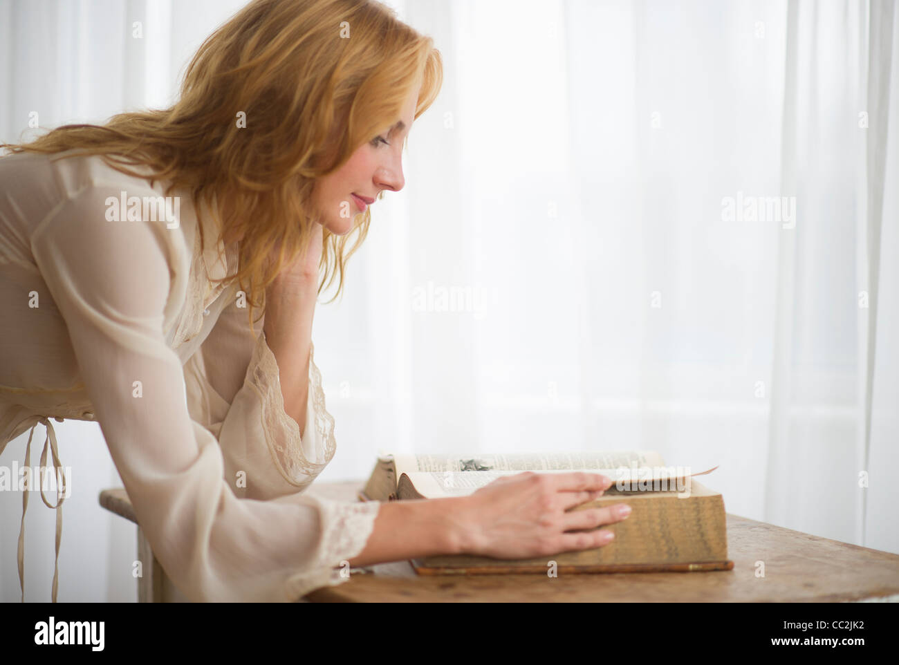 USA, New Jersey, Jersey City, Woman reading antique book - Stock Image
