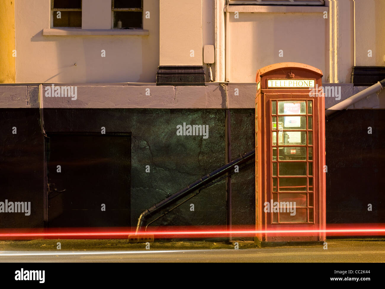 Night shot of UK phonebox with light trails from passing car. - Stock Image