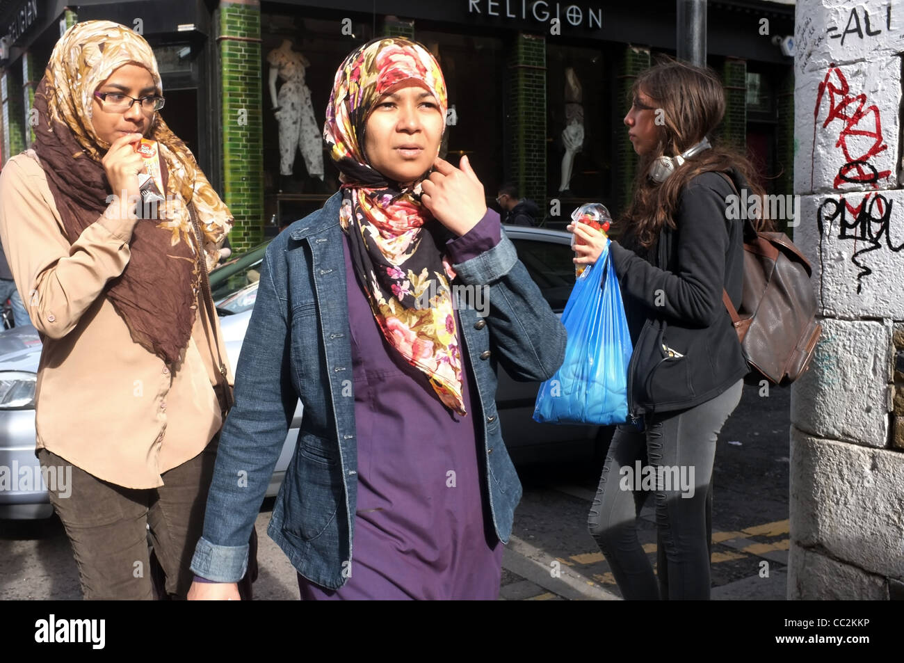 Two young Muslim women, in head scarves, walk along Brick Lane, in London's historic East End. - Stock Image