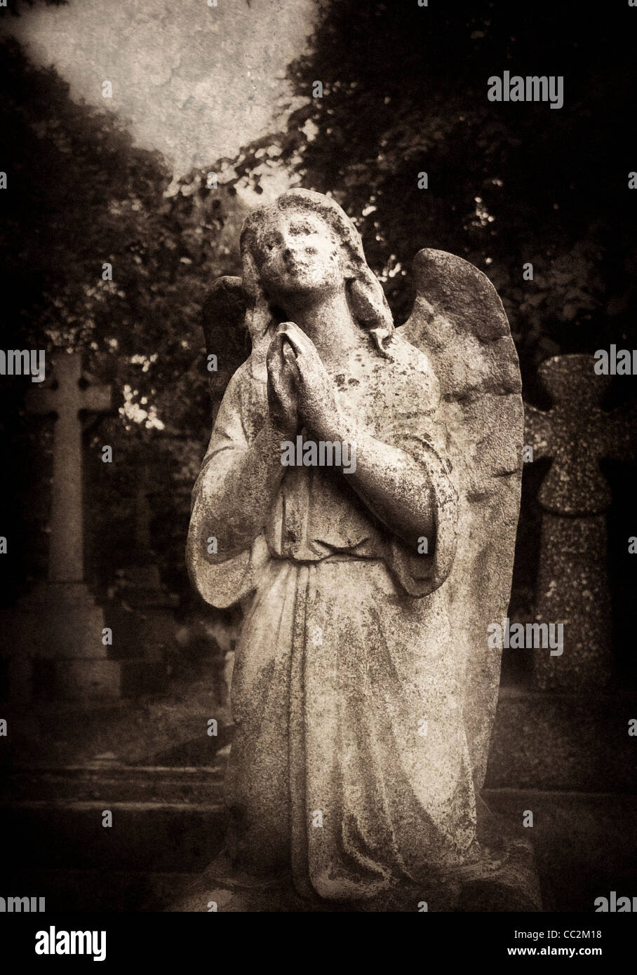 Statue of an female angel praying in Brompton Cemetery, London Stock Photo