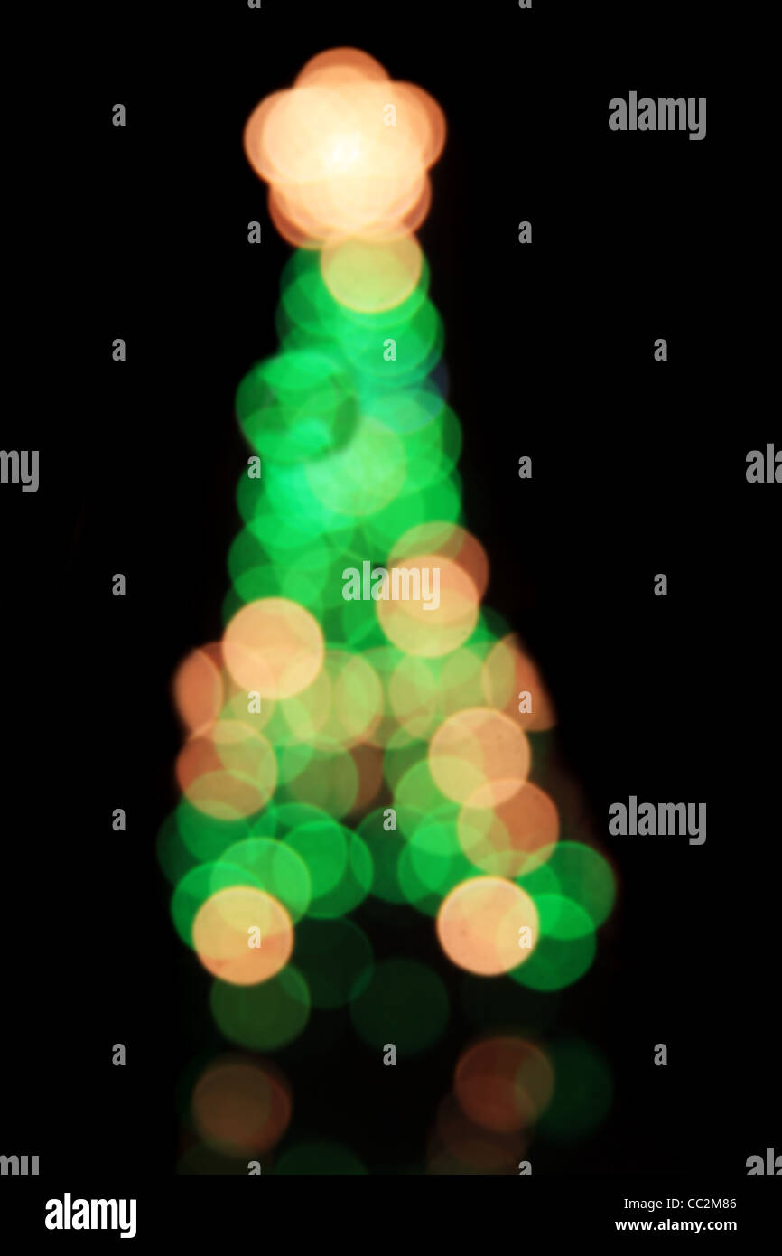 defocussed blurry Christmas tree on black background - Stock Image