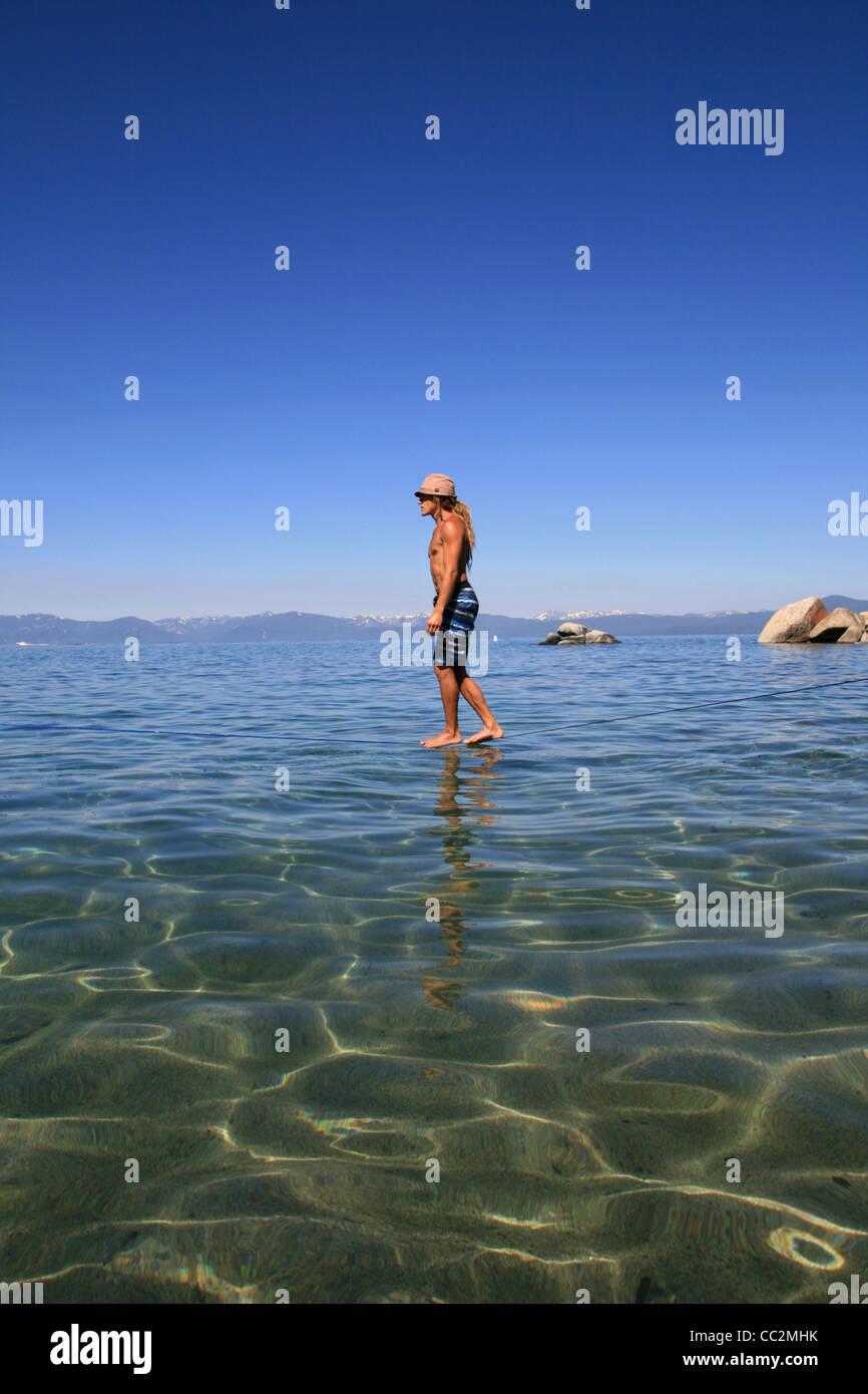 man slacklining above Lake Tahoe appears to walk on water - Stock Image