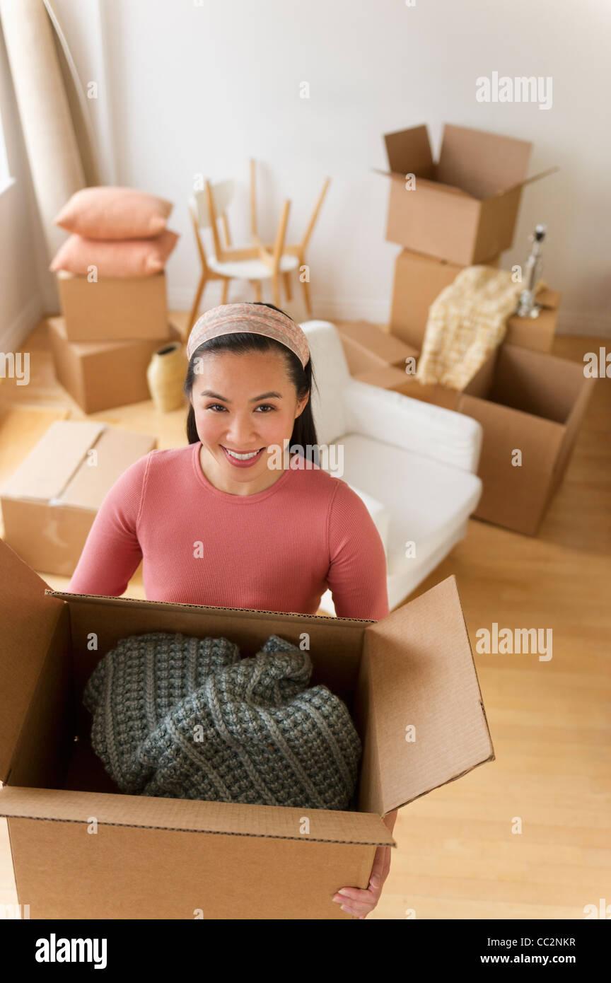 USA, New Jersey, Jersey City, Portrait of woman holding cardboard box - Stock Image