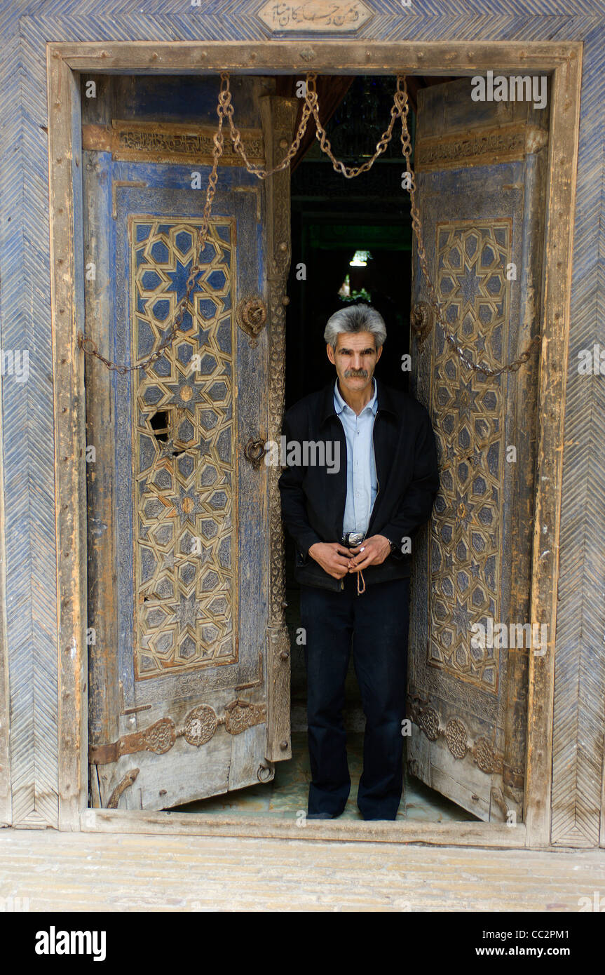 A custodian stands by one of the famous doors of the 15C mausoleum of the Sufi dervish Shah Nematollah Vali in Kerman, - Stock Image