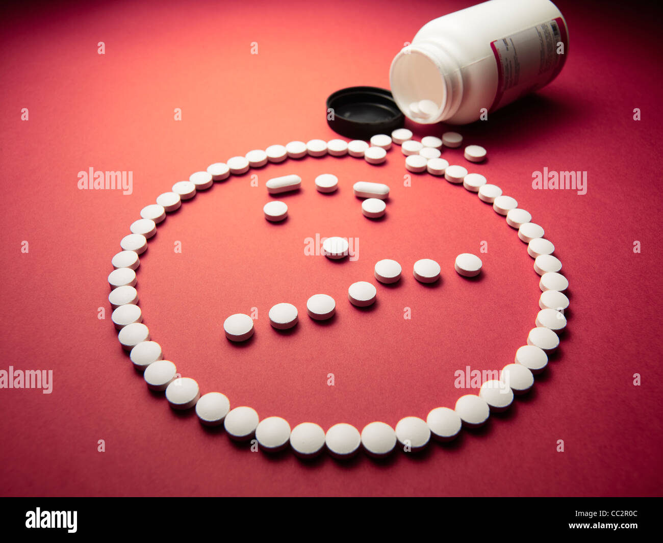 angry face made out of pills and drugs coming out of a bottle - Stock Image