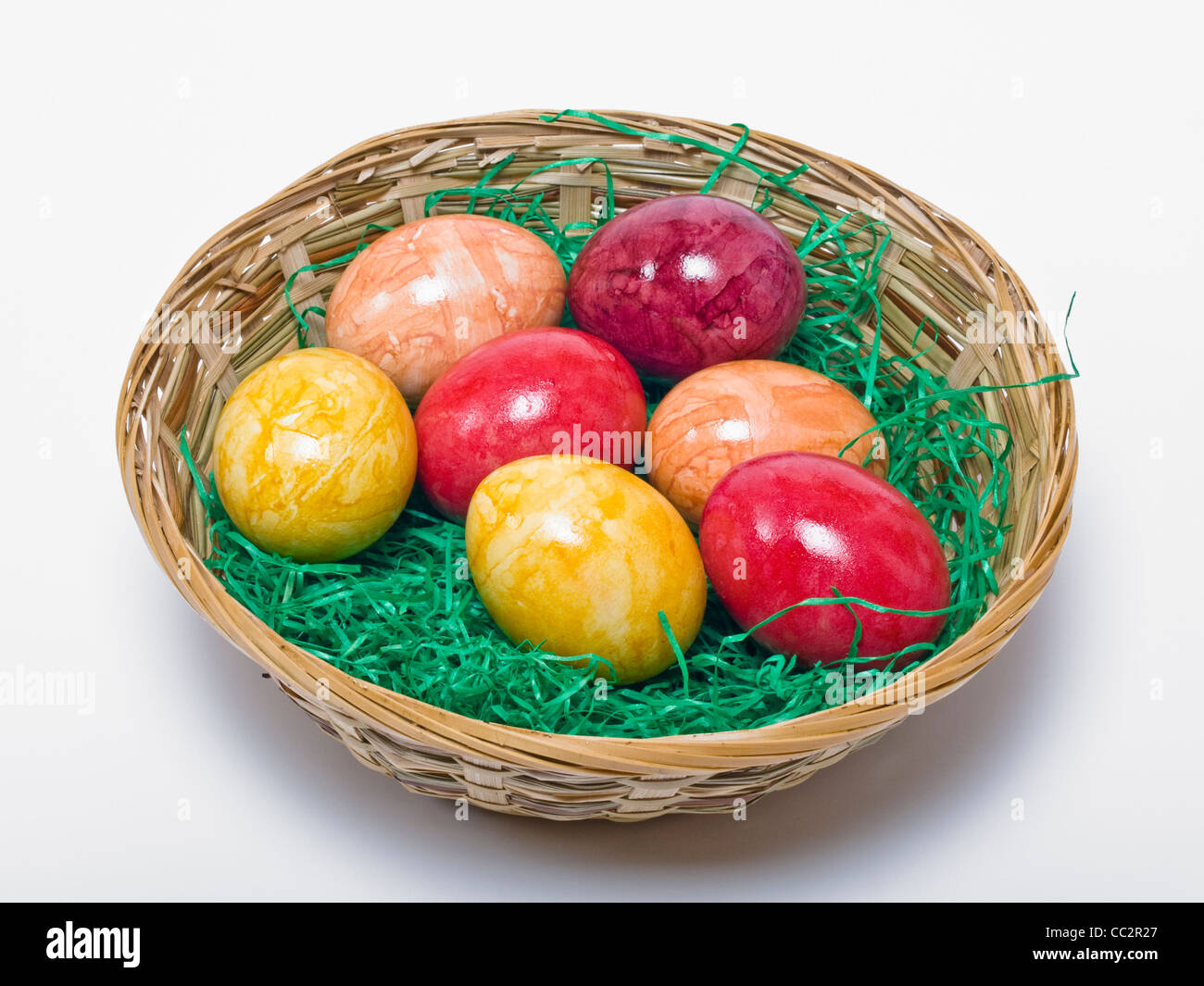 a Easter basket with grass some colored hen's eggs - Stock Image