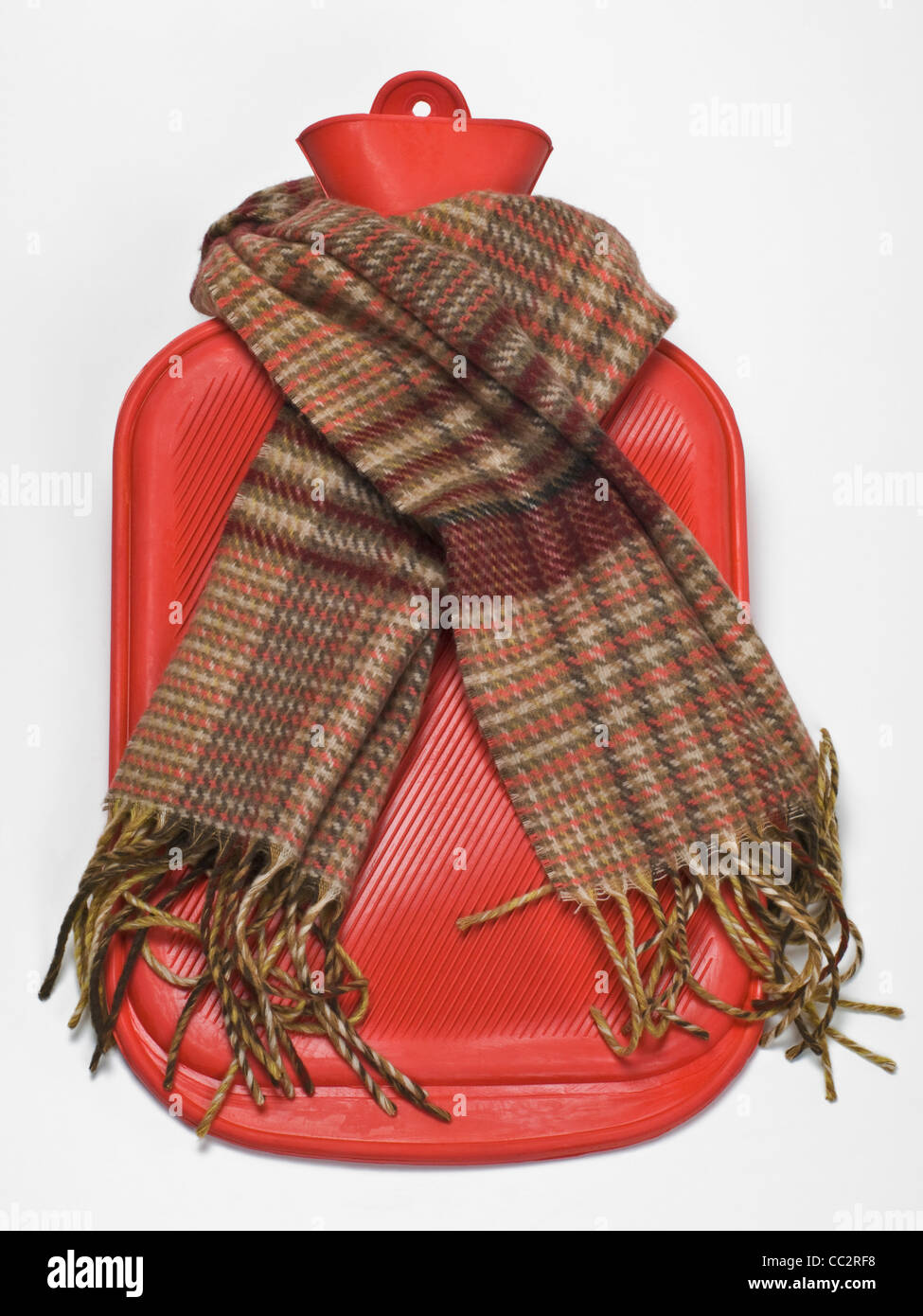 Detail photo of a a hot water bottle, a muffler is around - Stock Image