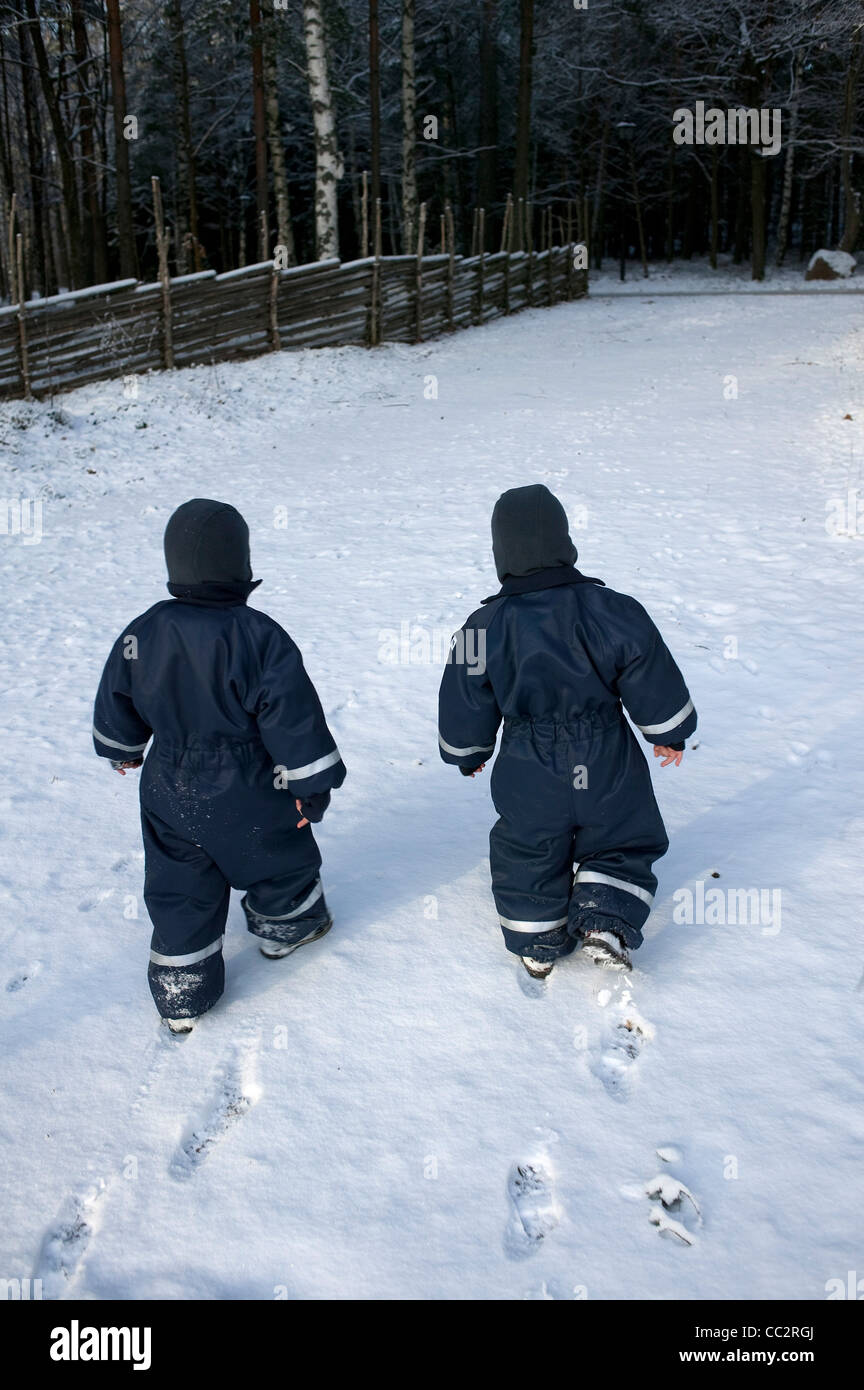 Twin boys wrapped in ski suits walking in snow, rear view, Sweden - Stock Image