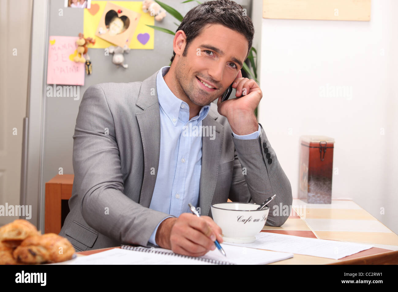 Man taking a business call over breakfast - Stock Image