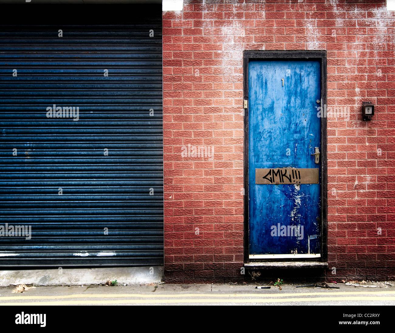 Derelict door with graffiti - Stock Image