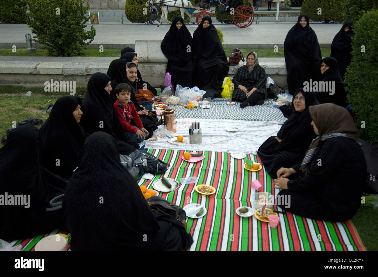 A group of ladies and some small children enjoy a Thursday evening picnic on the Maidan in Isfahan, Iran. - Stock Image