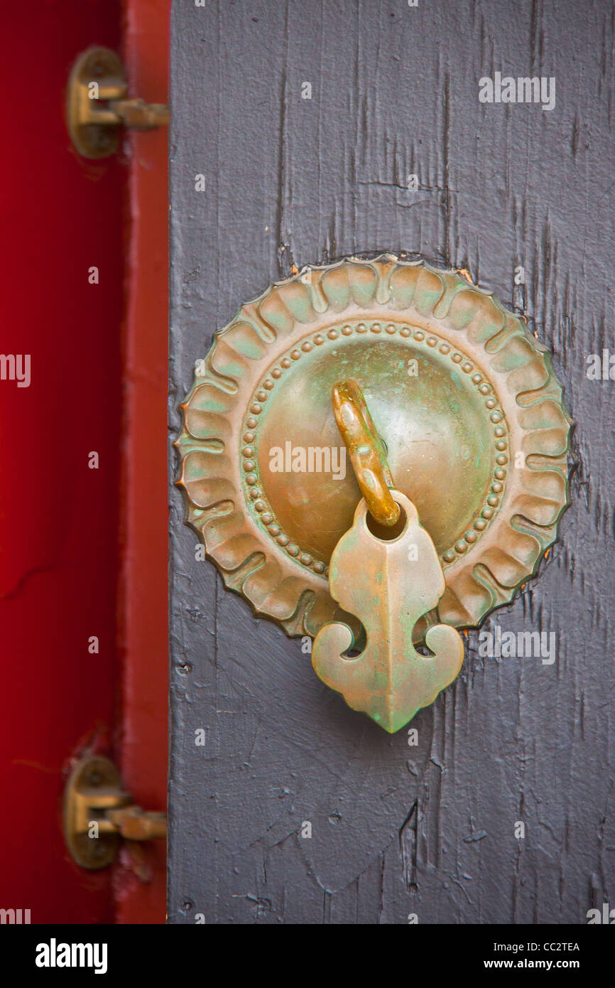 ancient solar Chinese bronze knob with an arrow handle and 2 hinges on a wood door painted in gray and red - Stock Image