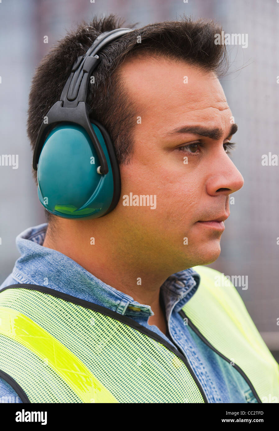 USA, New Jersey, Jersey City, Construction worker wearing reflective clothing and headphones - Stock Image