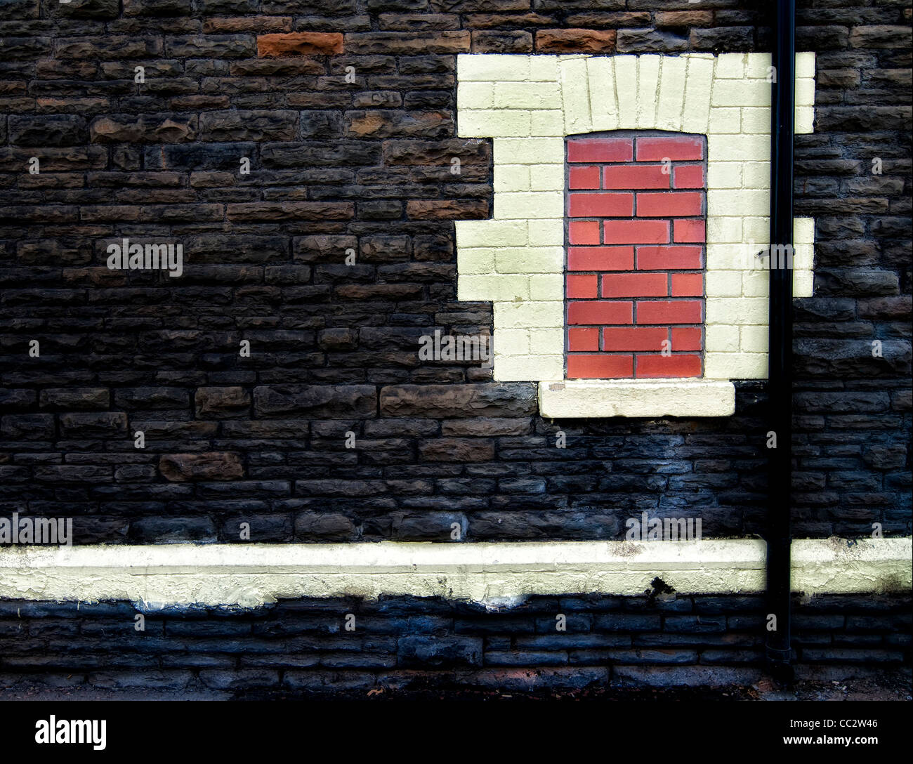 Derelict bricked in window with drainpipe - Stock Image