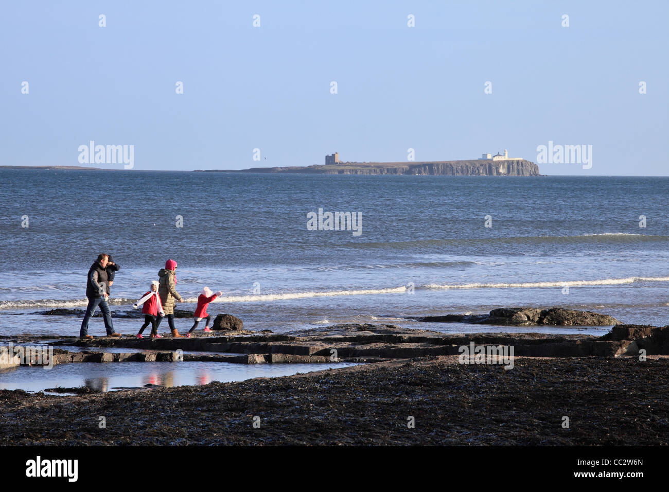 Young family walking on the beach at Bamburgh with the Inner Farne island in the background north east England UK Stock Photo