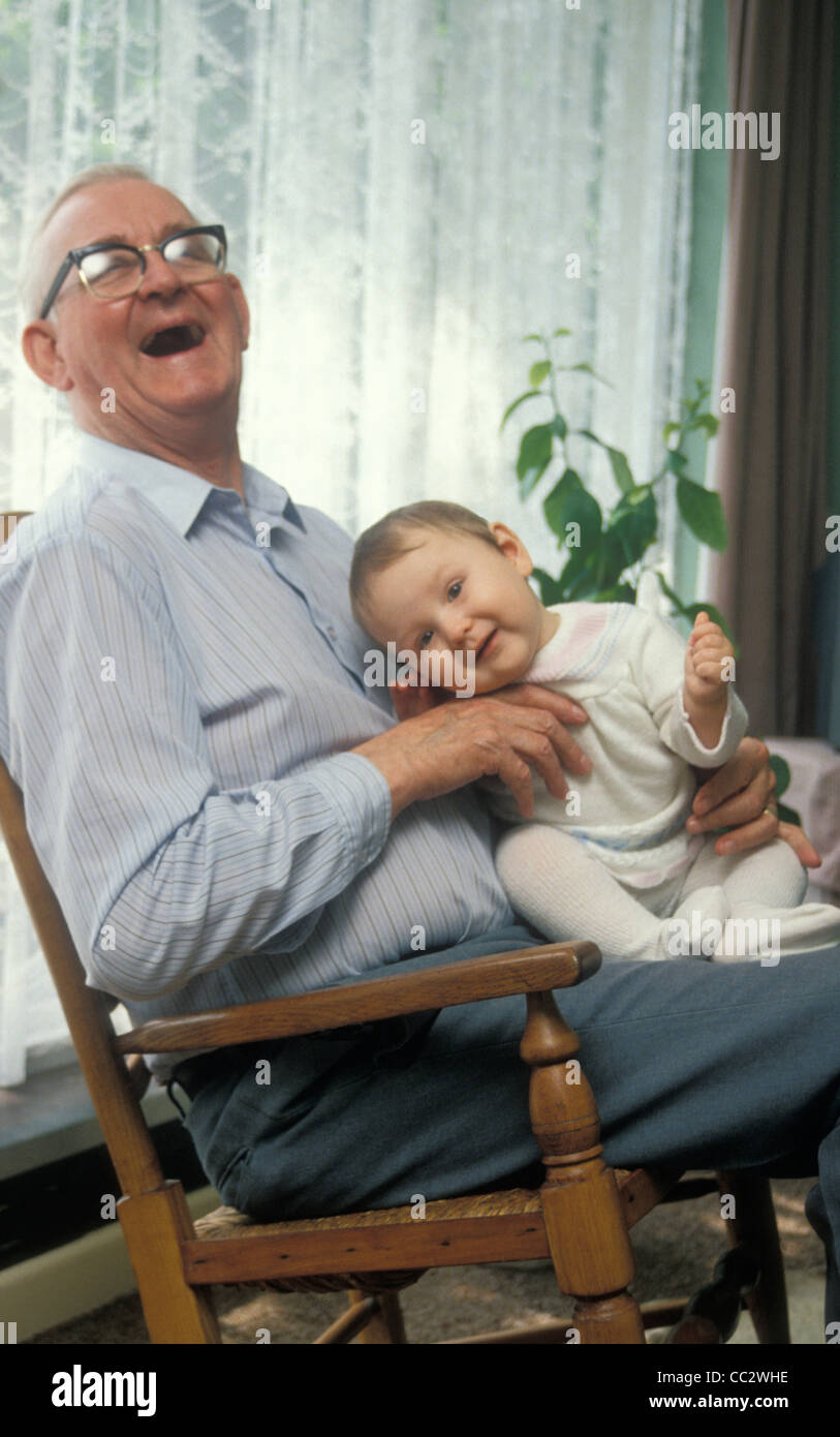 Laughing Grandpa Holding Baby In Rocking Chair Stock Photo