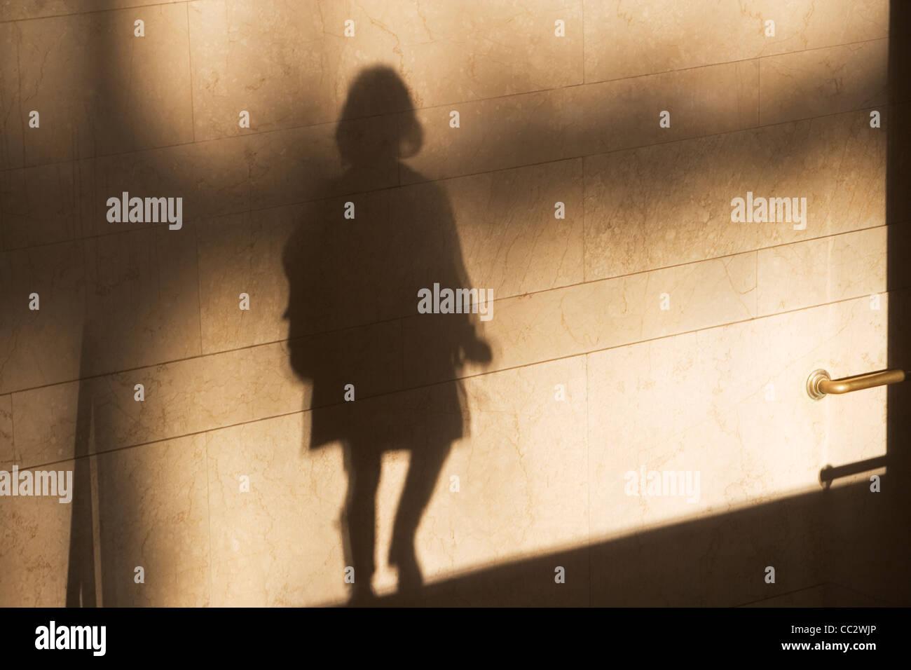 USA, New York City, Shadow of single male pedestrian on sunlit wall Stock Photo