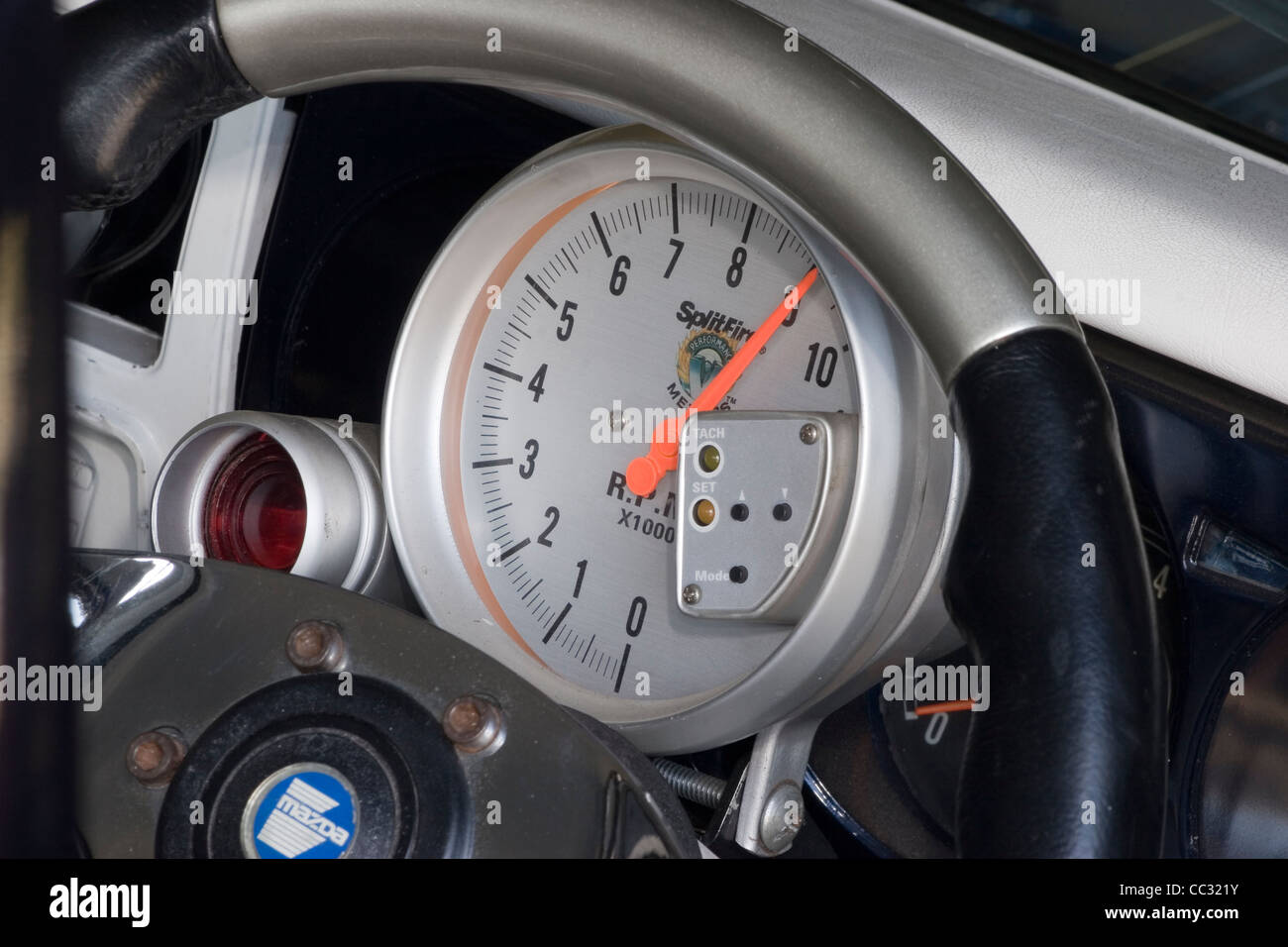 Analogue tachometer tacho rev counter dial gauge on the dash fascia of a custom race car. - Stock Image