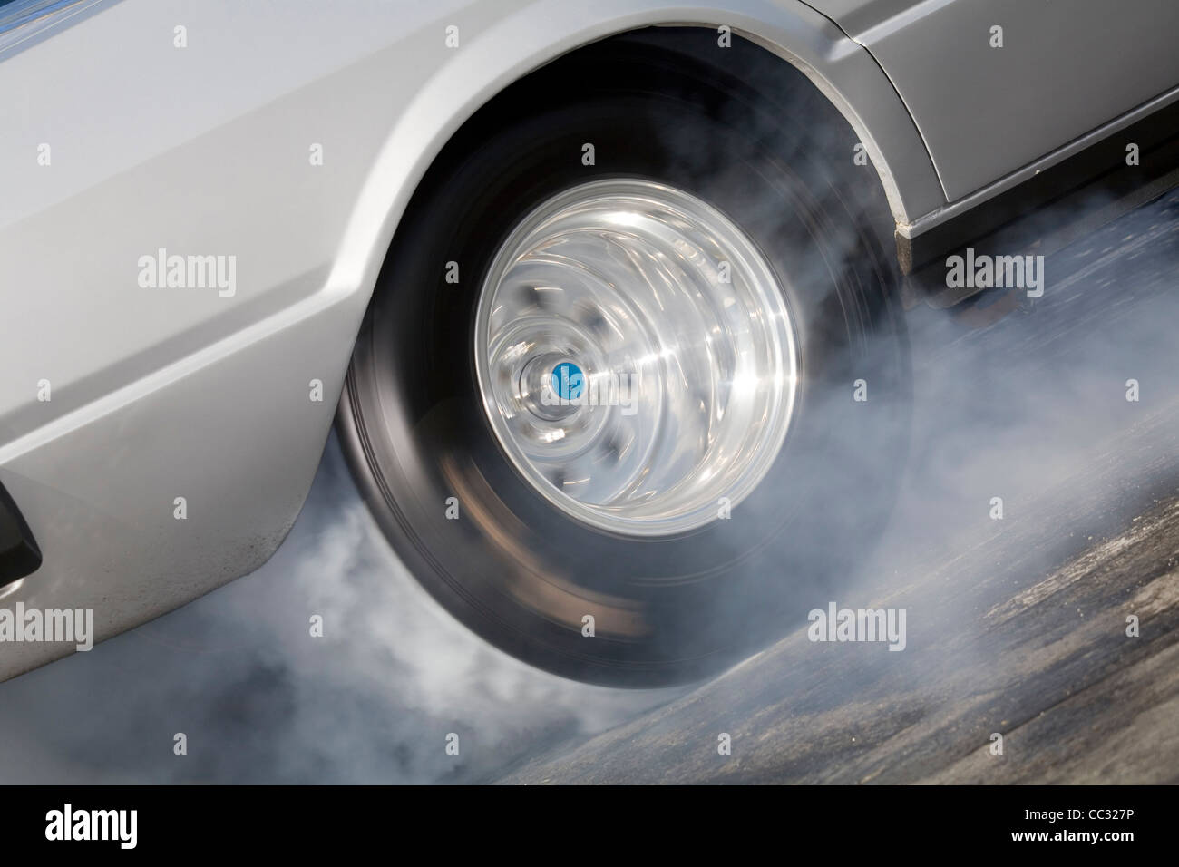 spinning wheel of a drag racing car skidding and producing burning rubber tire smoke. Stock Photo
