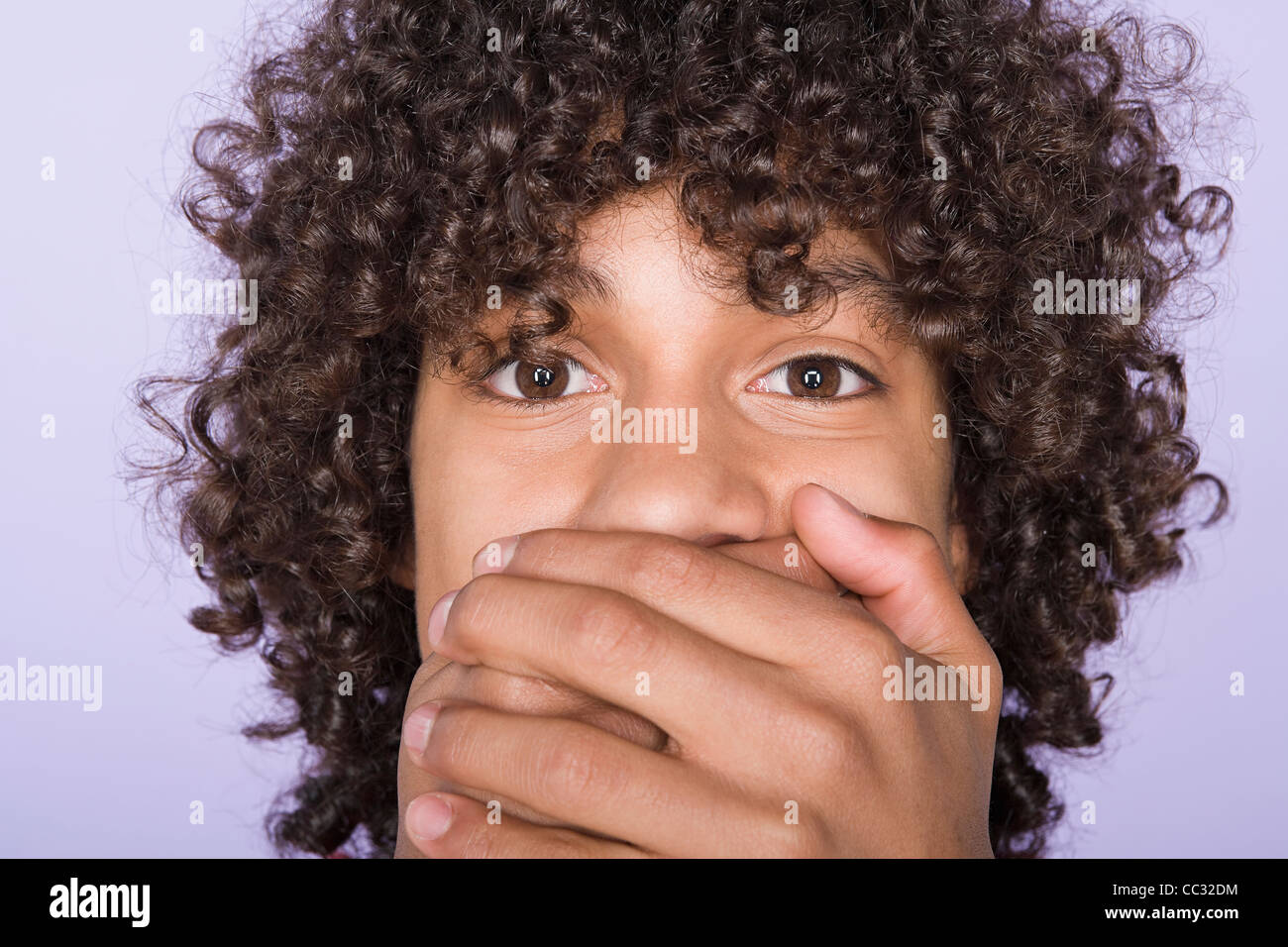 Portrait of teenage boy (14-15) covering mouth with hands Stock Photo