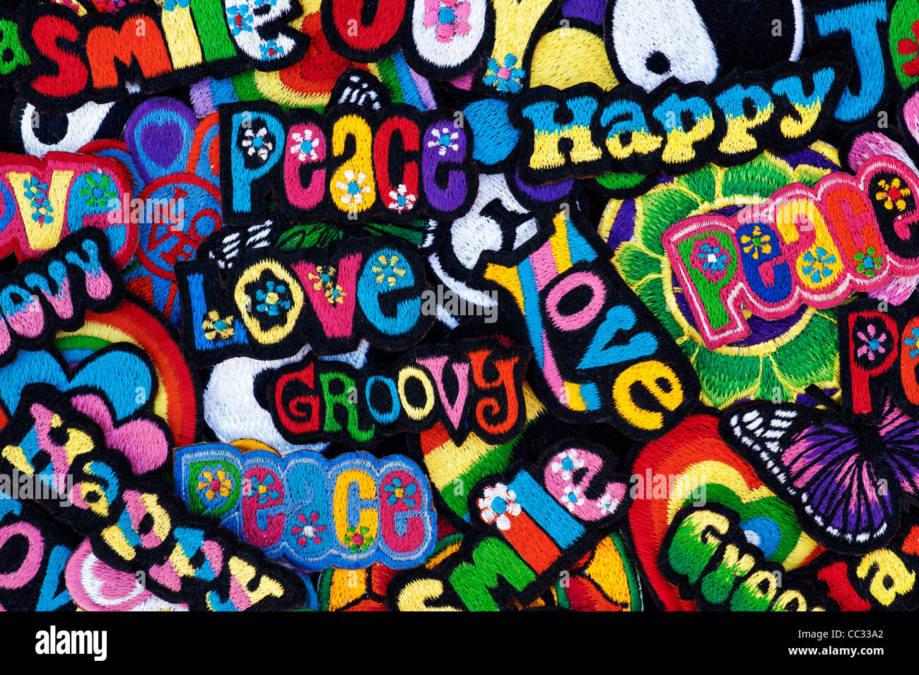 Embroidery iron on patches of Multicoloured Love, Peace, Happy, Smile, Joy and Groovy words on a black background - Stock Image