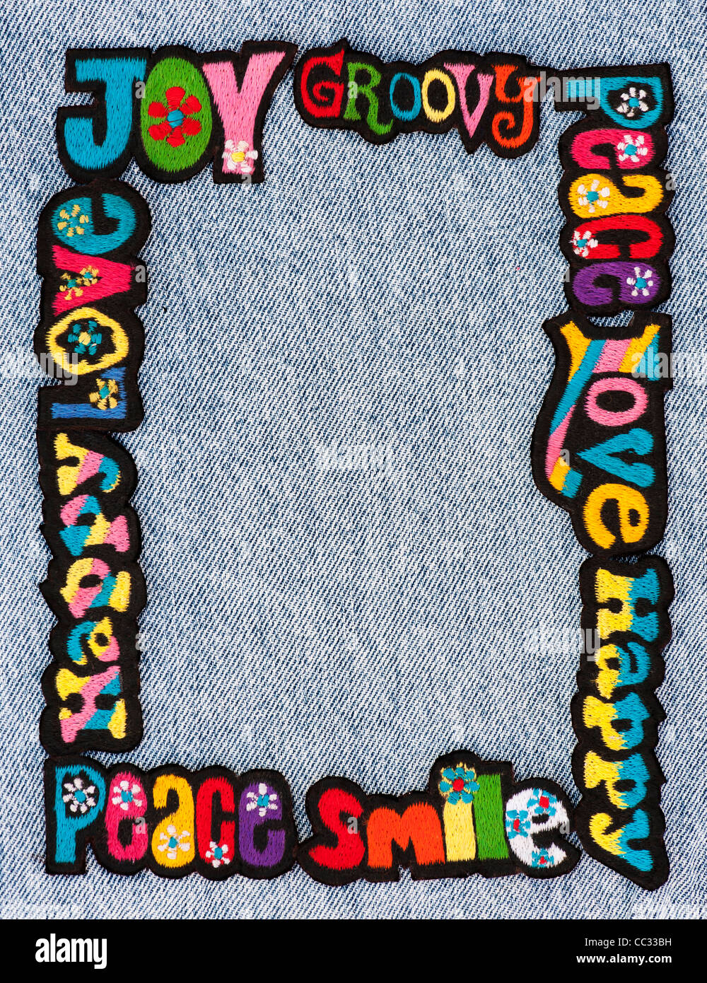 Embroidery iron on patches of Multicoloured Love, Peace, Happy, Smile and Joy words on a denim jean background - Stock Image