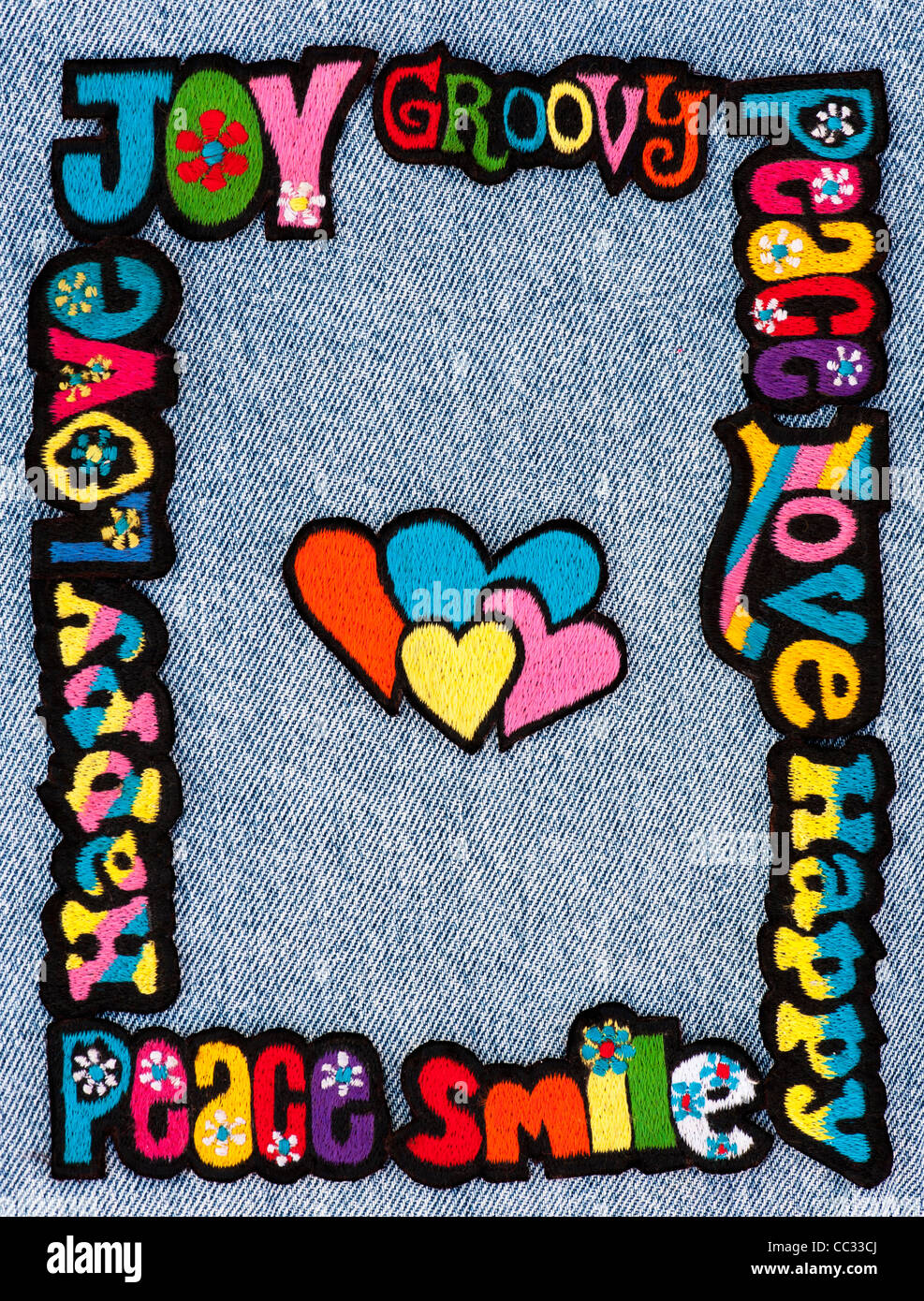 Embroidery iron on patches of Multicoloured Love, Peace, Happy words with hearts on a denim jean background - Stock Image