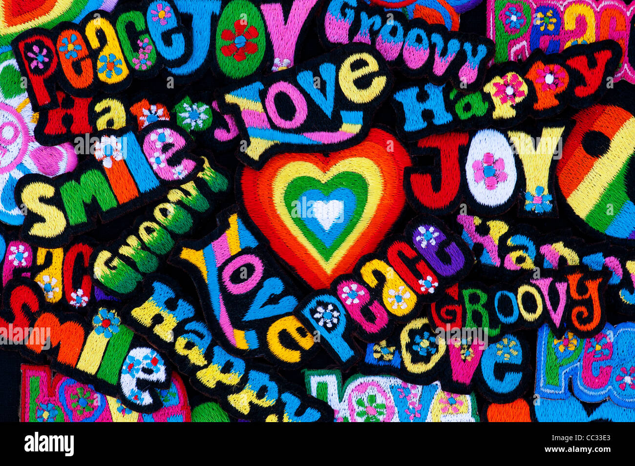 Embroidery iron on patches of Multicoloured Love, Peace, Happy words with hearts on a black background - Stock Image
