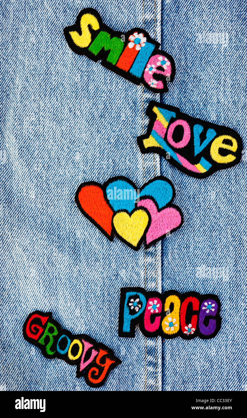 Embroidery iron on patches of Multicoloured Love, Peace and Smile words with hearts on a denim jean background - Stock Image