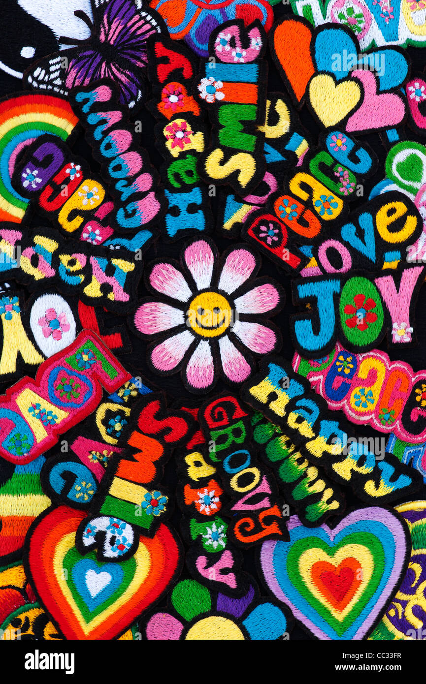 Embroidery iron on patches of Multicoloured Love, Peace, Happy, Smile, Joy, Groovy words with a flower on a black - Stock Image